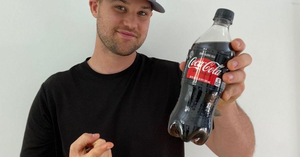 man holding a bottle of coke