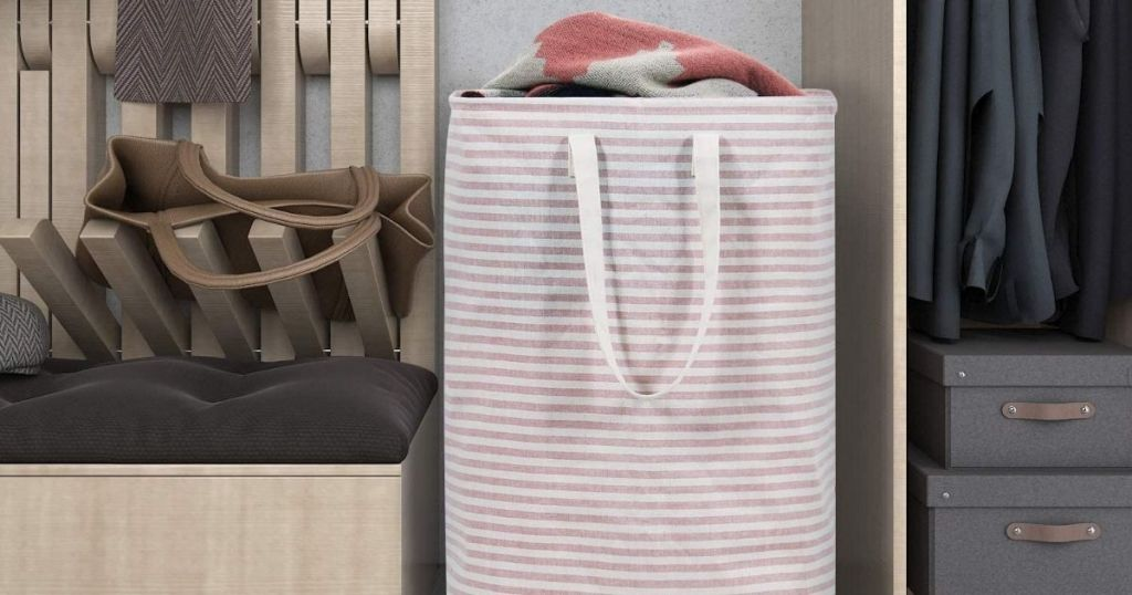 hamper in a closet with clothes in it