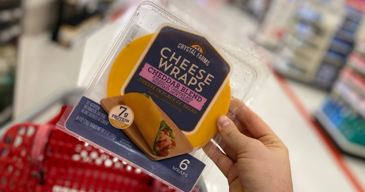 hand holding up a pack of cheese wraps above a Target cart in a store aisle