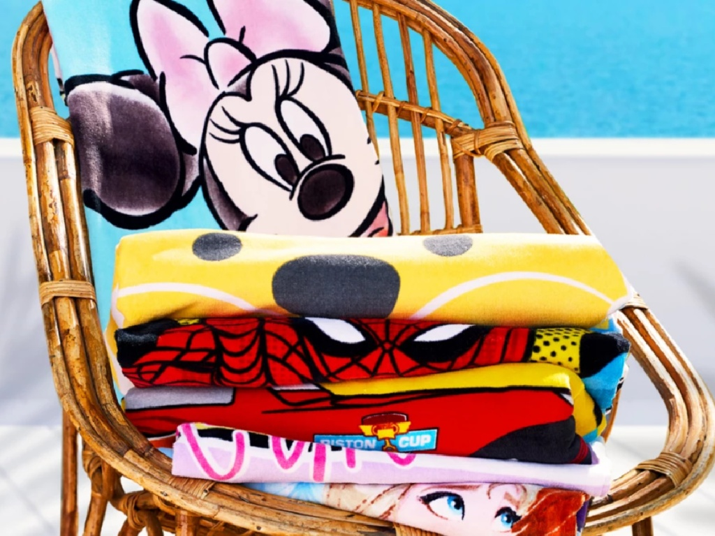 stack of disney beach towels on a chair
