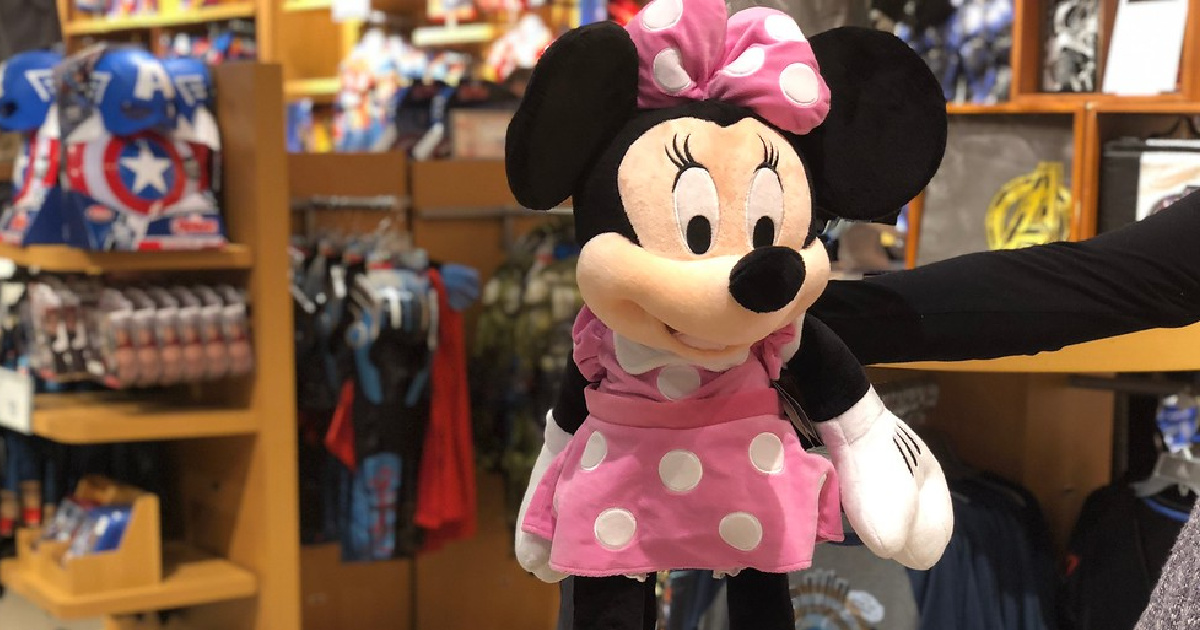 hand holding up a large pink and white minnie mouse plush doll in a store