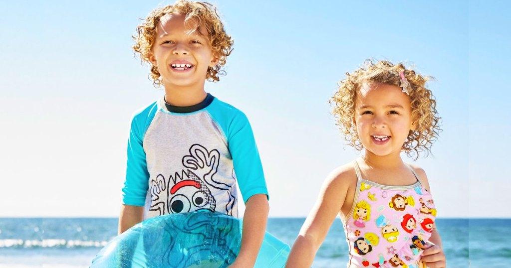 two kids at beach in disney swimwear