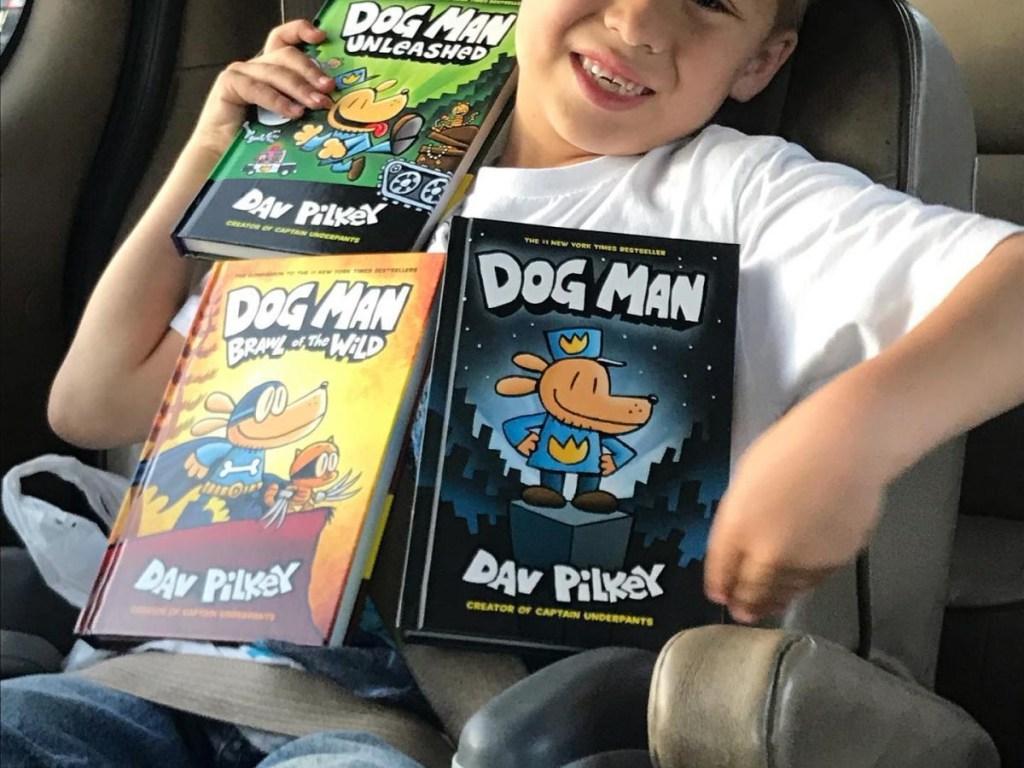 boy holding a variety of Dog Man books