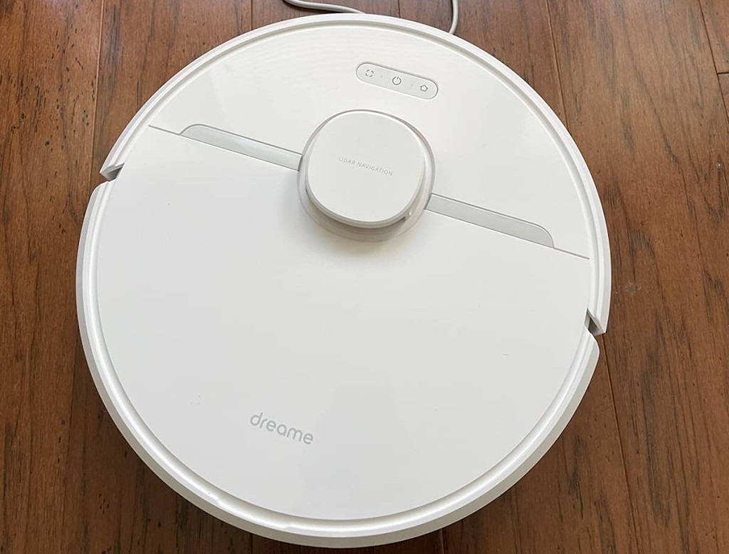 white robot vacuum cleaner cleaning wood floor