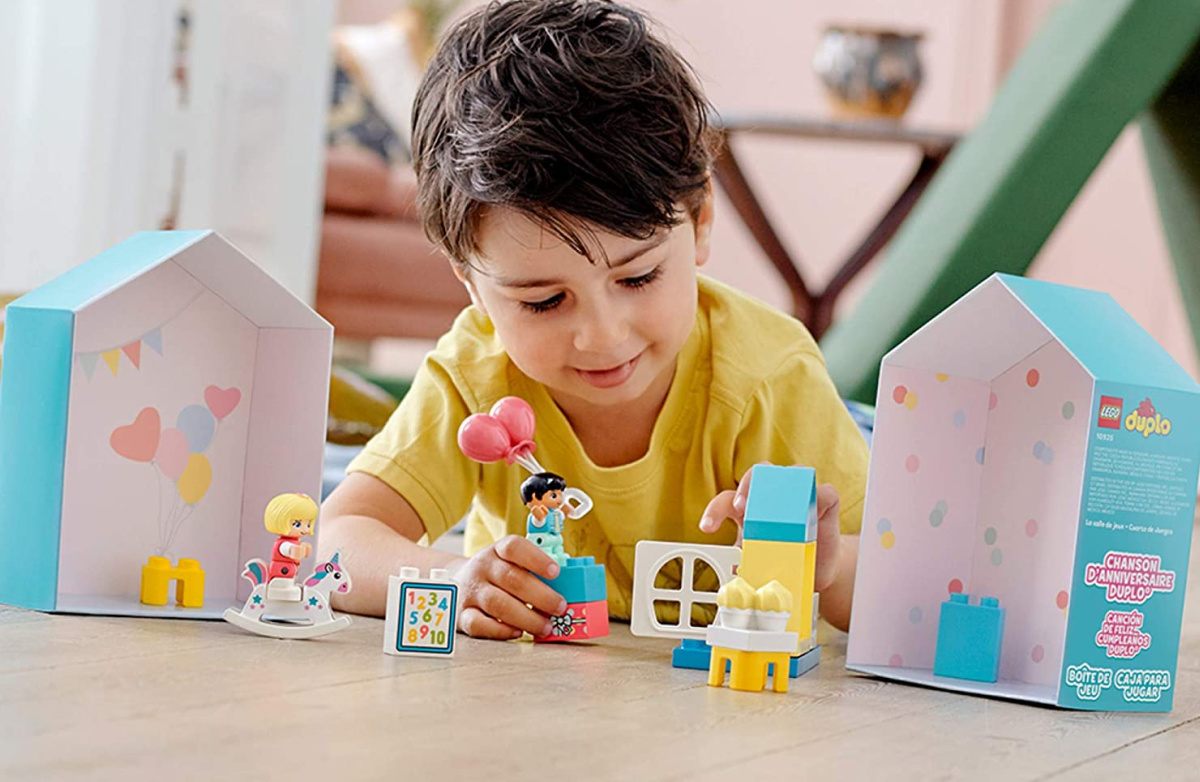 kid building a LEGO town playhouse set on table