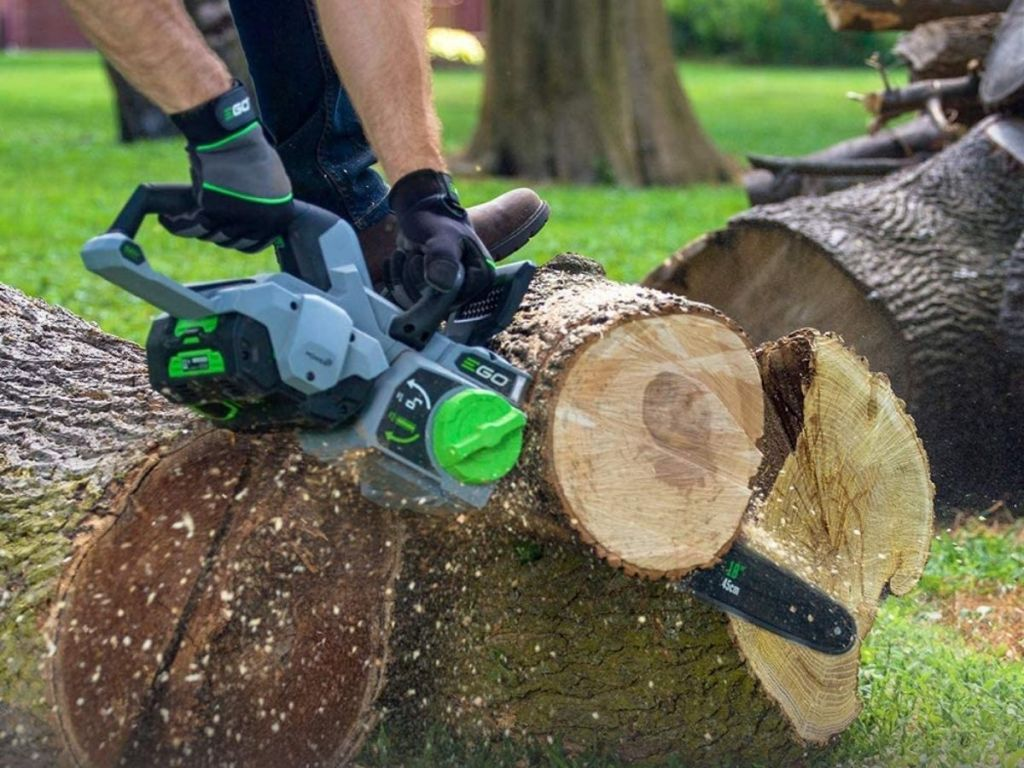 person using chainsaw on log