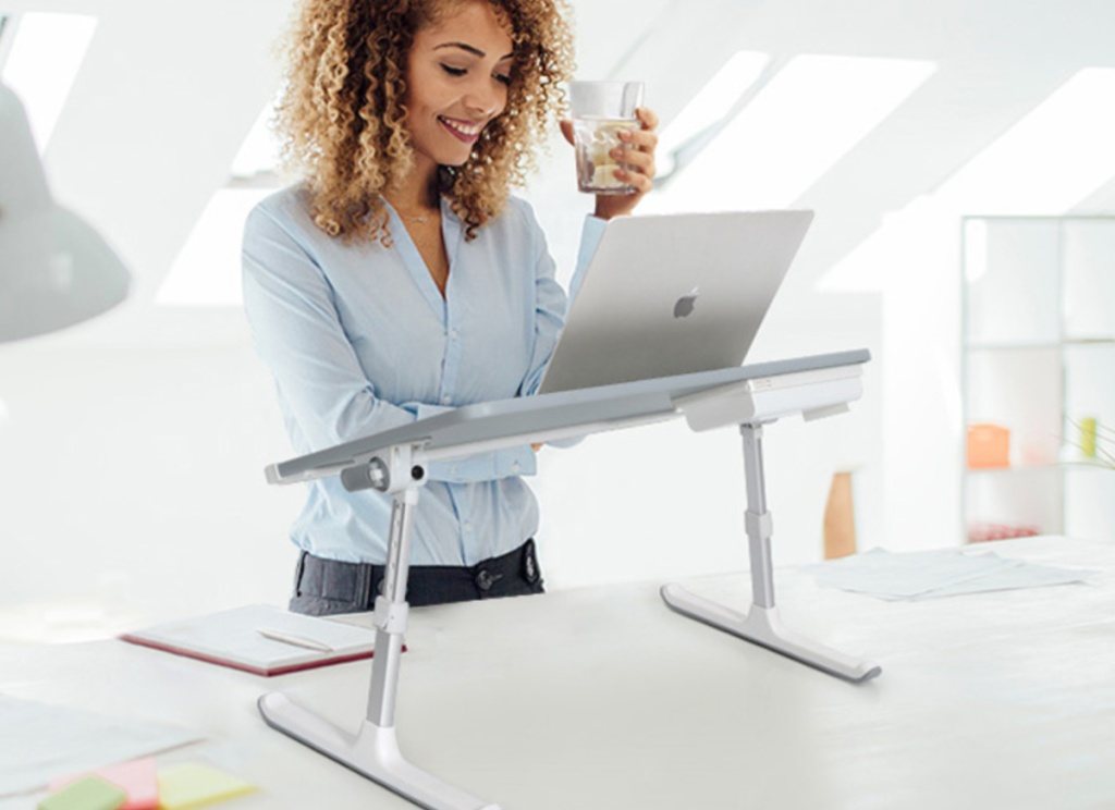 woman standing in front of aa grey laptop desk on a table