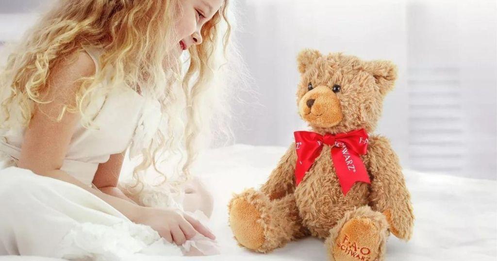 girl looking at a plush bear
