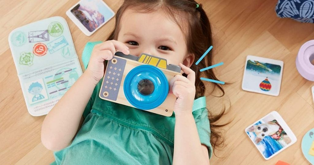 girl holding up wooden camera to her face