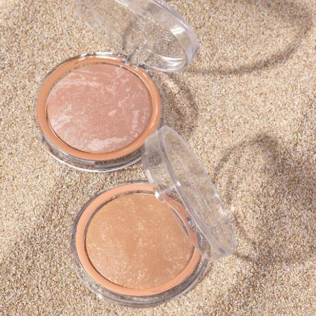two containers of highlighter in sand