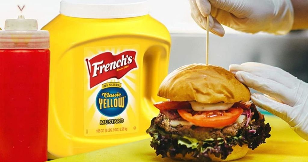 Huge tub of French's Yellow Mustard next to a burger
