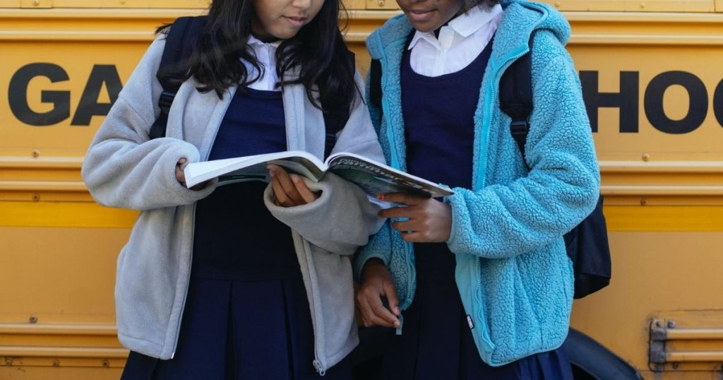 two girls in front of a school bus wearing school uniforms and reading a book