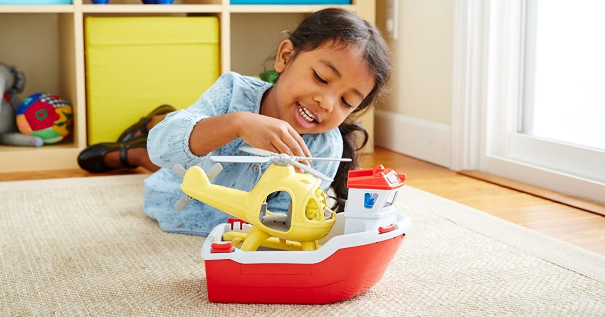 Green toys rescue boat on the floor with a little girl playing with the helicopter on top of the boat