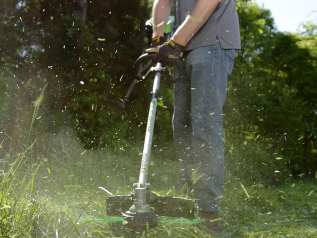 man holding a greenworks trimmer