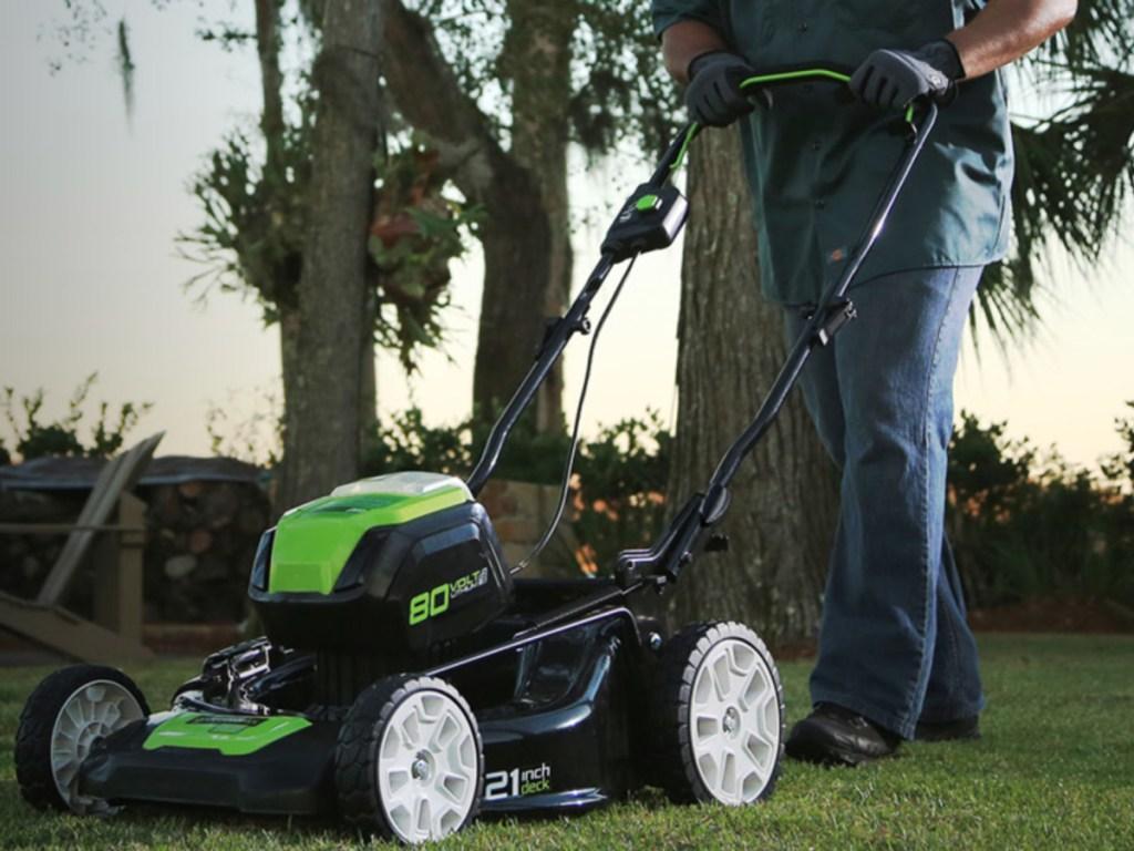 man pushing a greenworks lawn mower