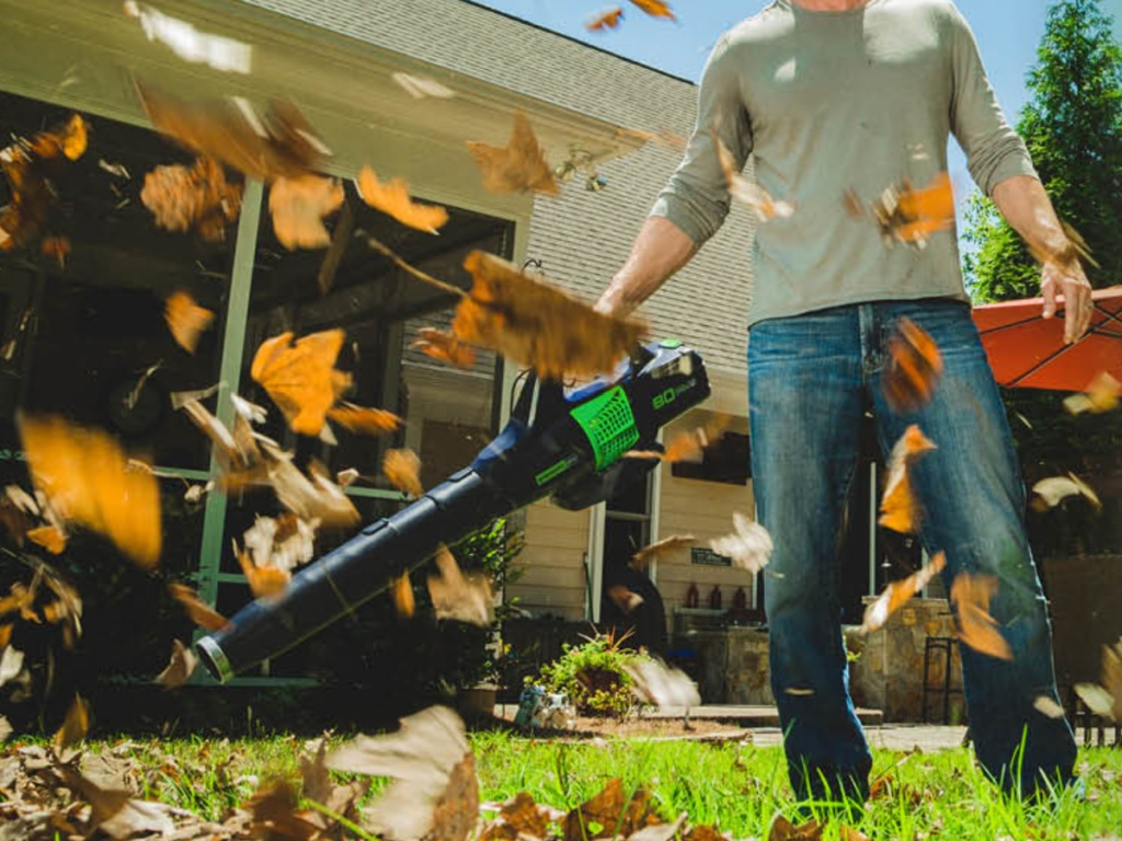 man holding a leaf blower outside