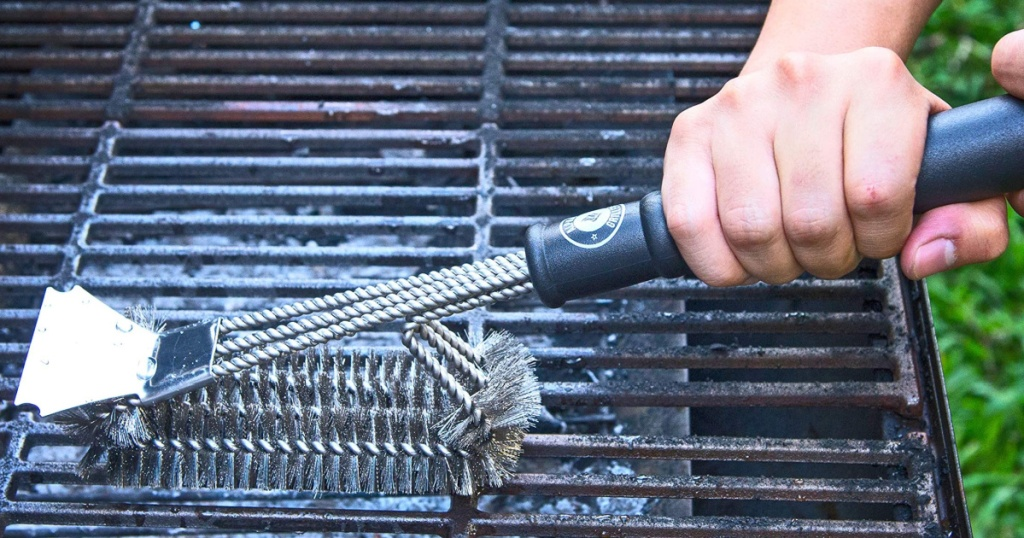 hand holding a grill brush on top of a grill
