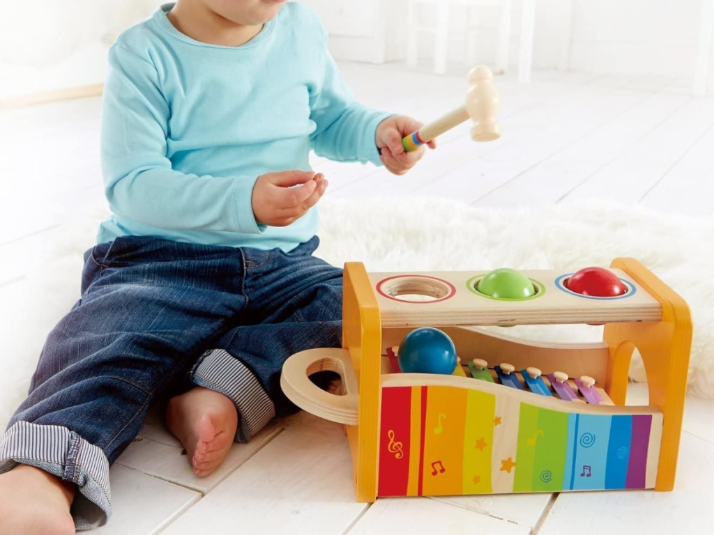 child sitting on the floor with a toy wooden xylaphone