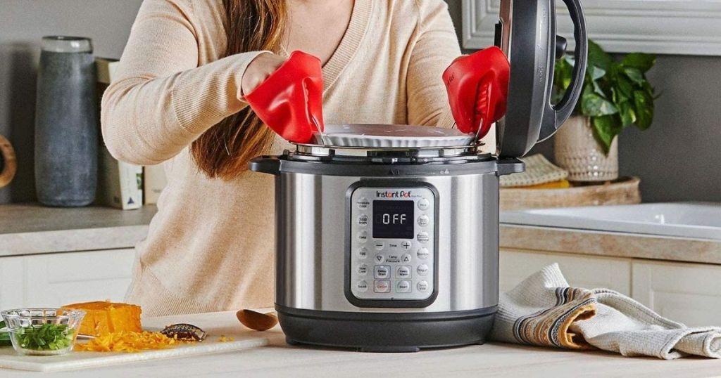 hand grabbing insert from pressure cooker
