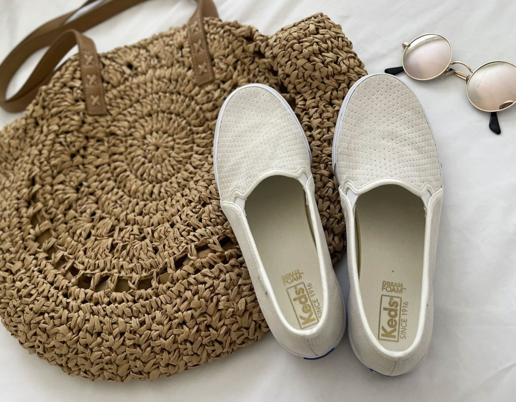 white slip on shoes on a purse next to sunglasses