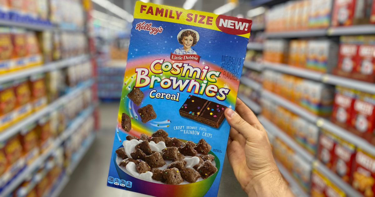 hand holding up a family size box of little debbie cosmic brownies cereal in a store aisle