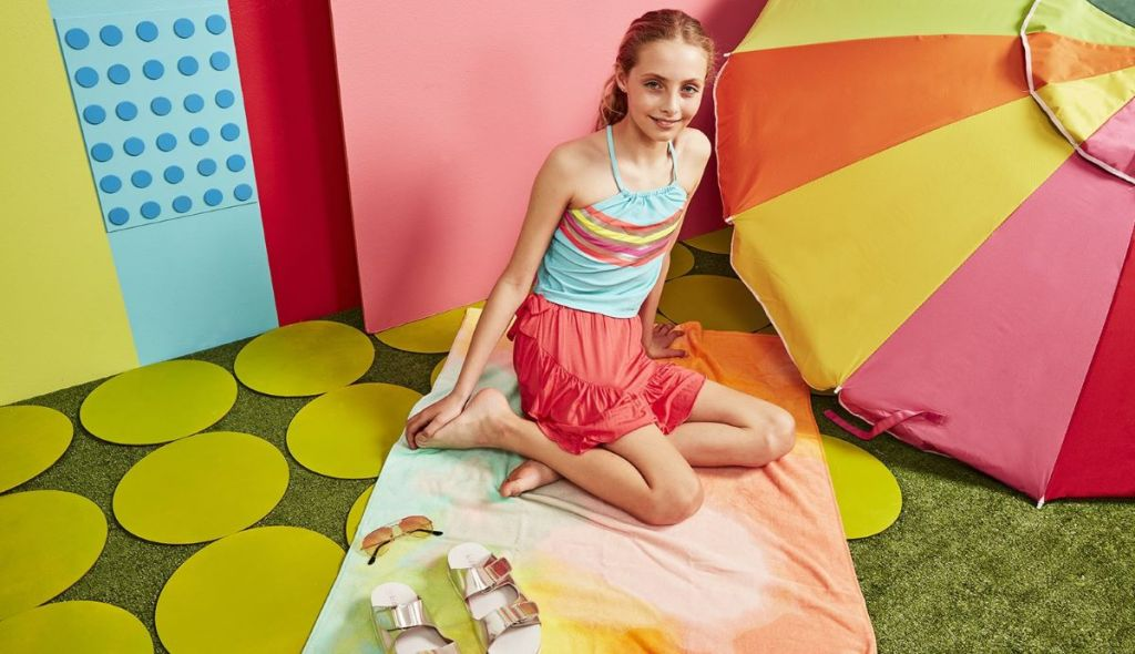girl sitting on a becah towel