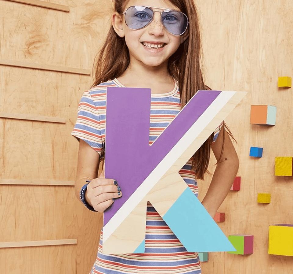 girl holding a large letter K