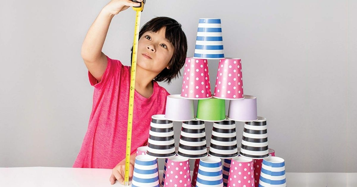 Boy measuring stacked paper cups with a measuring tape