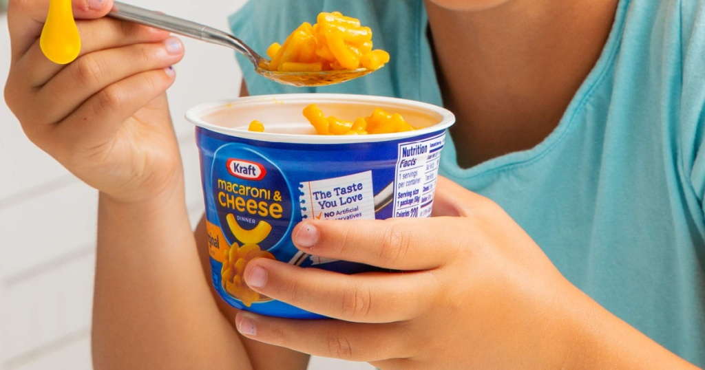 childholding kraft mac and cheese cup
