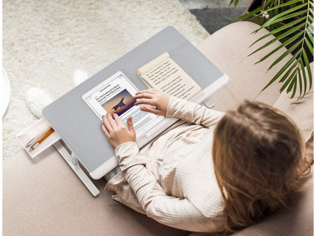 girl using laptop desk on couch