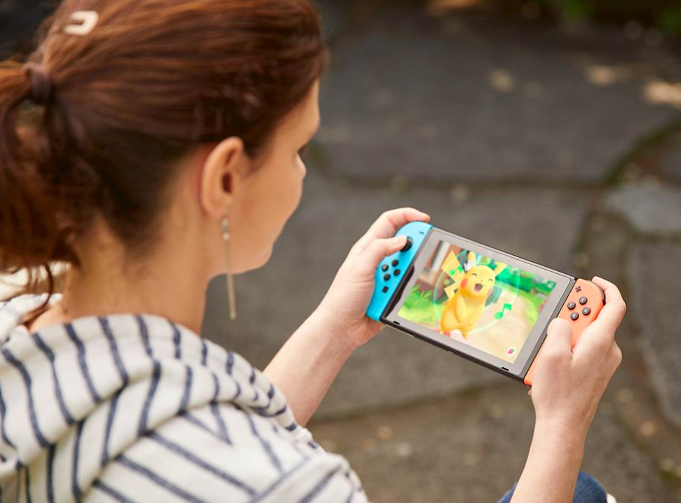 woman holding a Nintendo Switch and playing a pokemon game