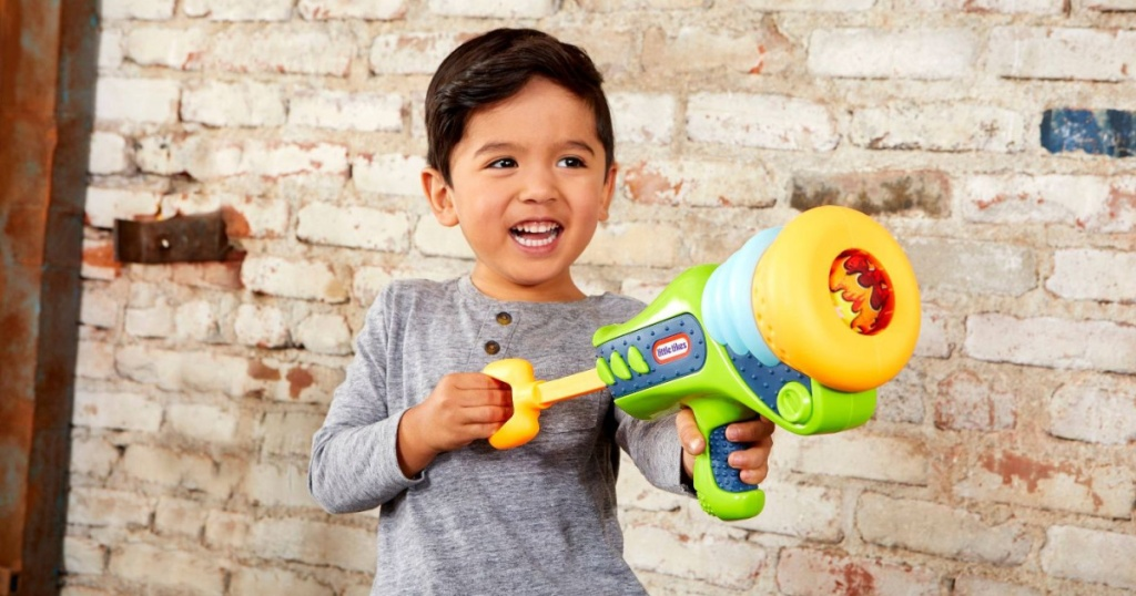 boy playing with a little tikes blaster in front of a brick wall