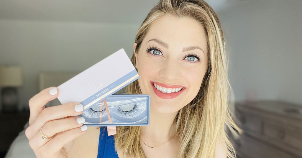 woman with blonde hair holding up set of lashes