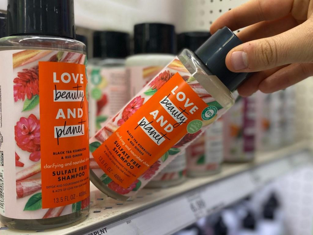 hand grabbing bottle of sulfate-free shampoo