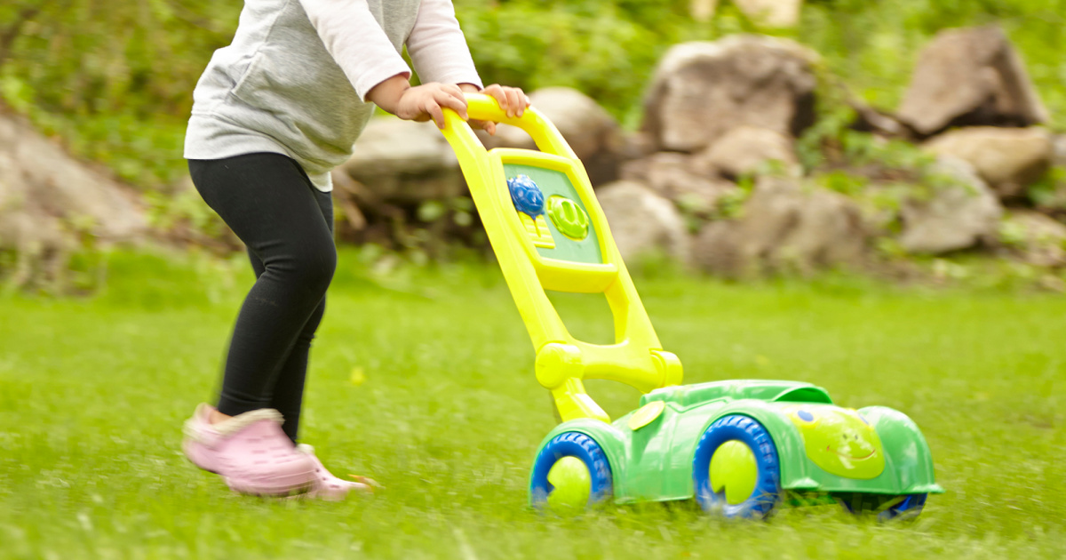 young child pushing a turtle shaped toy lawn mower outside