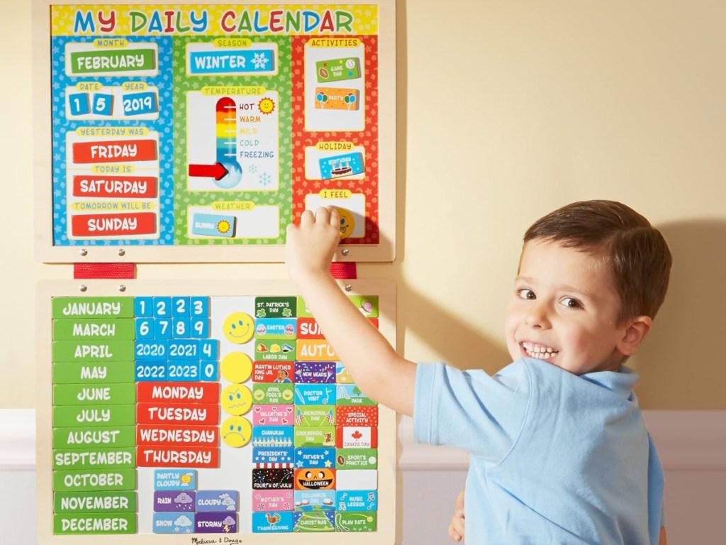 little boy next to a melissa and doug daily calendar