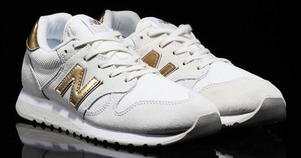 pair of white and gold new balance sneakers