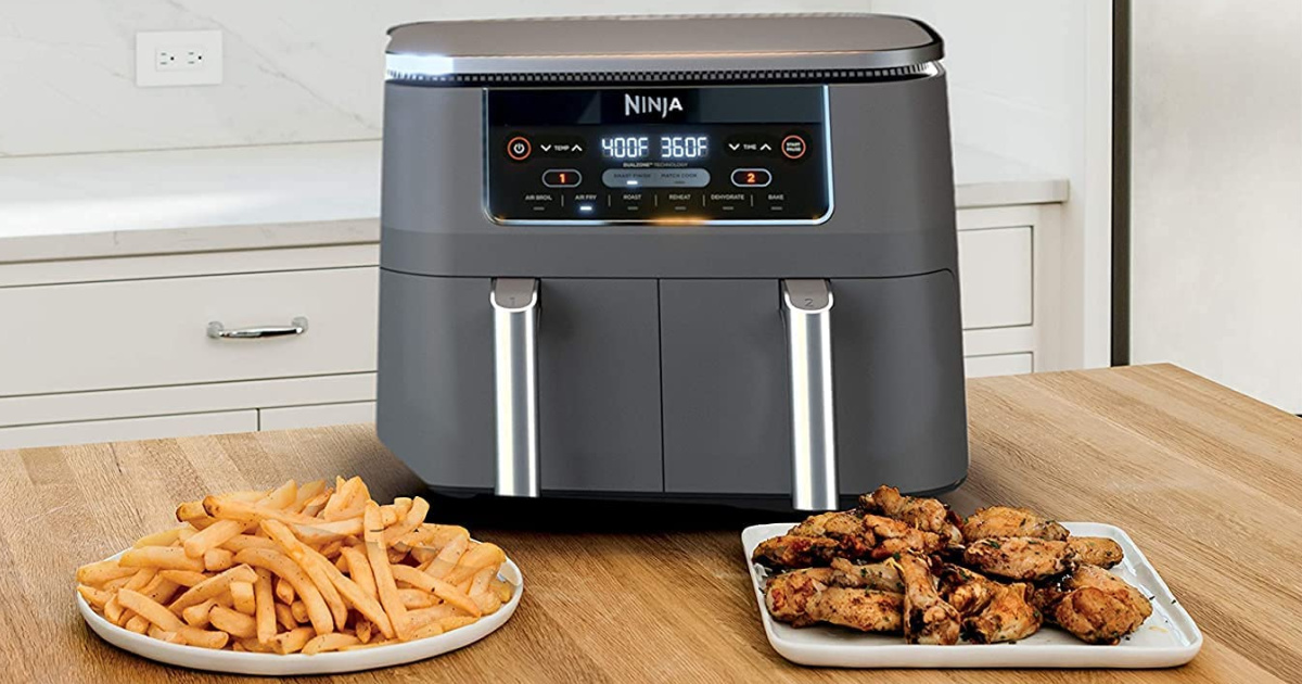 air fryer on a table between a plate of fries and a plate of chicken wings