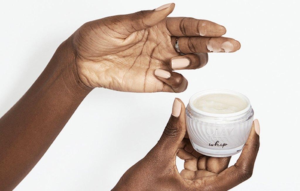 woman holding up jar of olay whip moisturizer