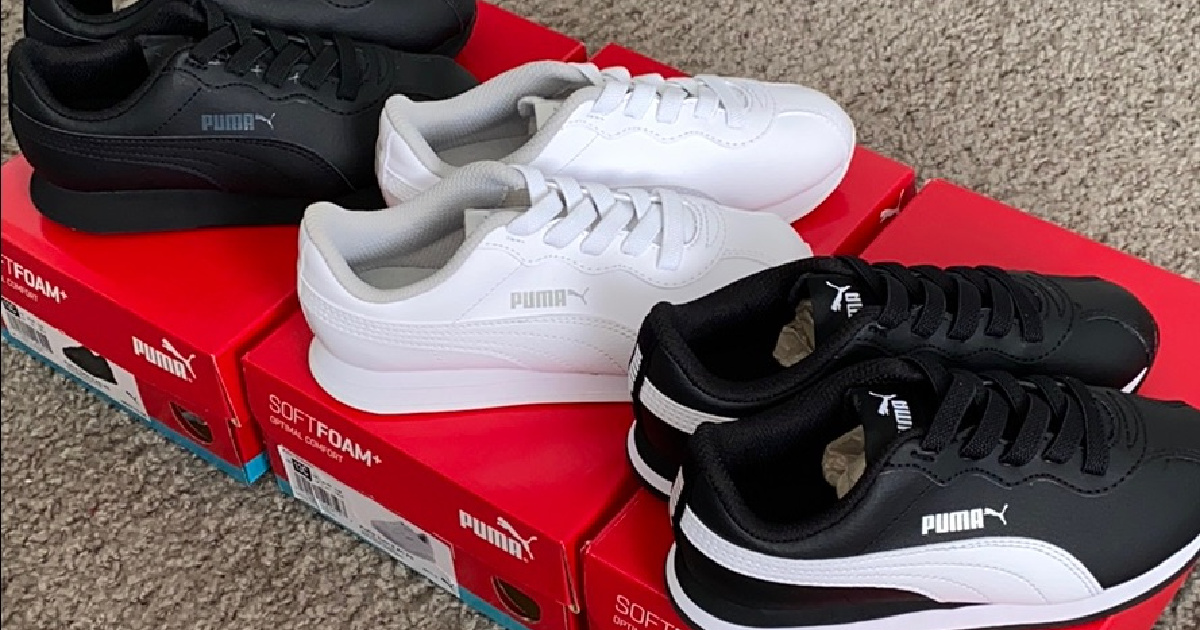 three pairs of kids' sneakers on shoe boxes on carpet floor