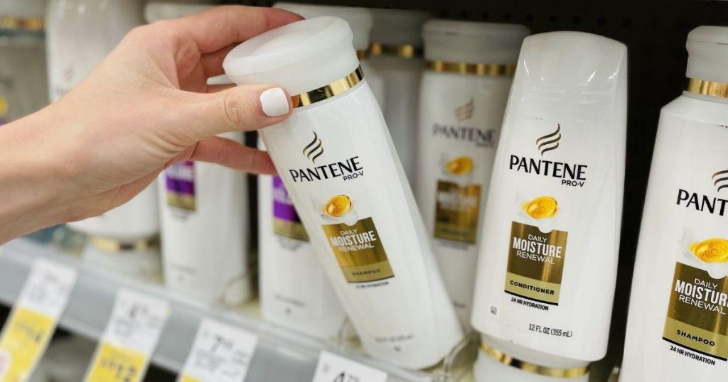 hand holding a bottle of Pantene