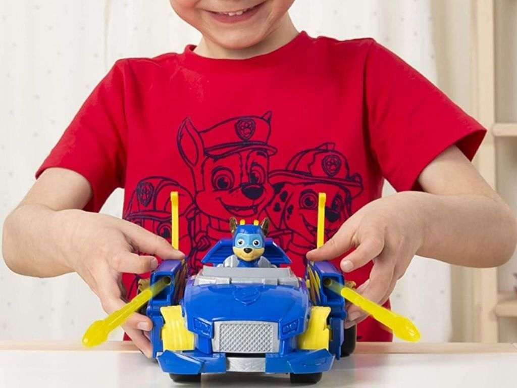 little boy playing with Paw Patrol toy car