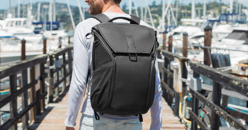 man holding a black photography backpack