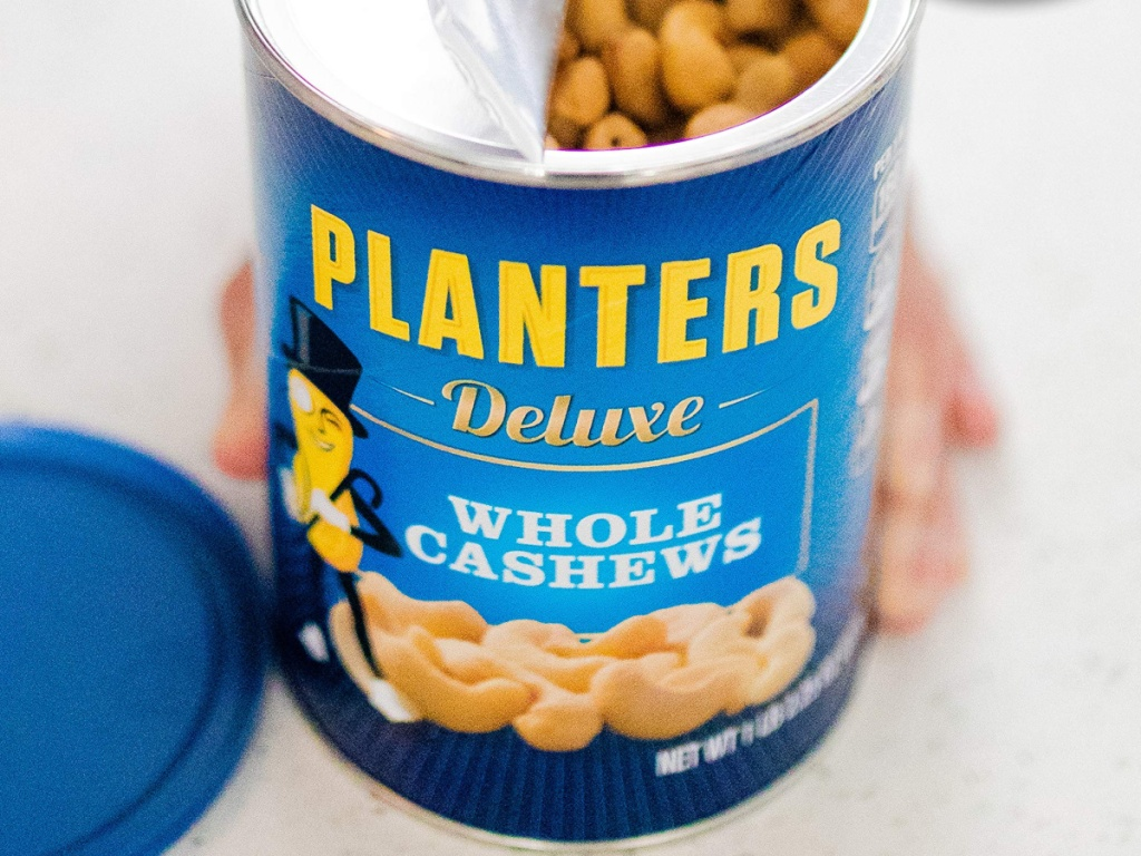 hand holding a planters cashew canister