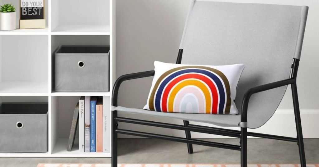 sling chair with a pillow on it next to a bookcase