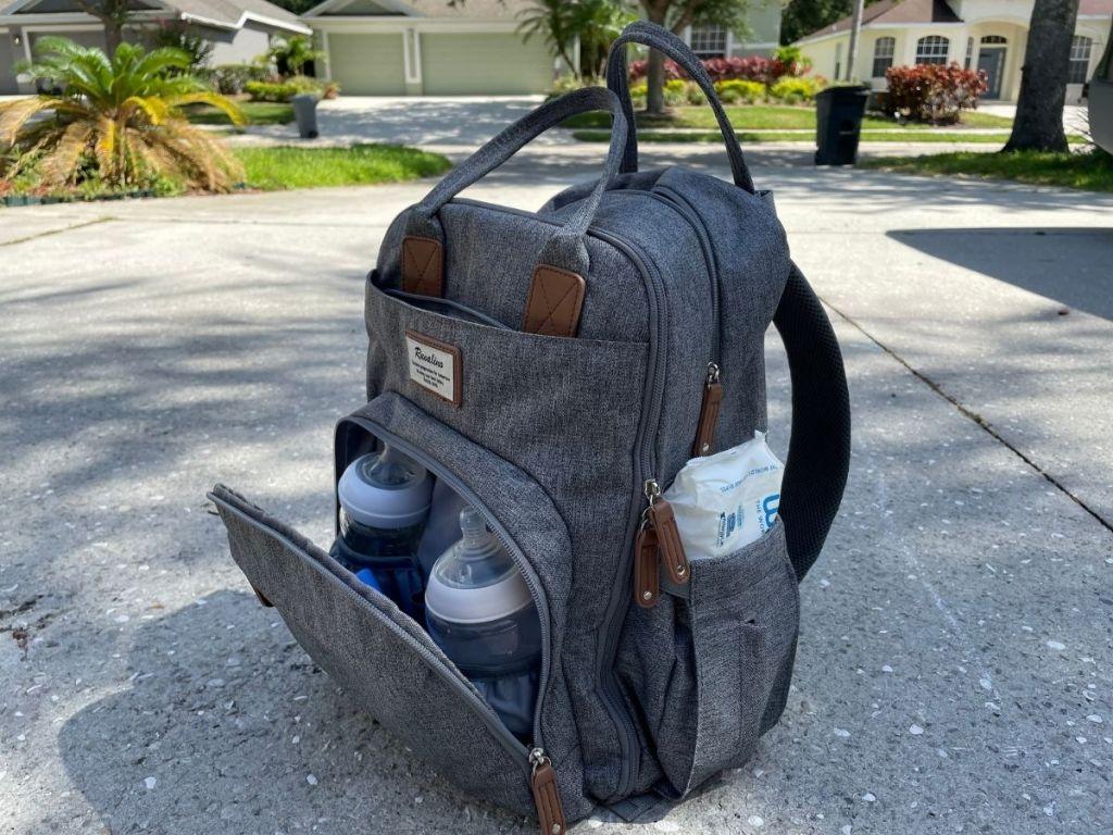 gray diaper bag backpack slightly opened to reveal baby bottles