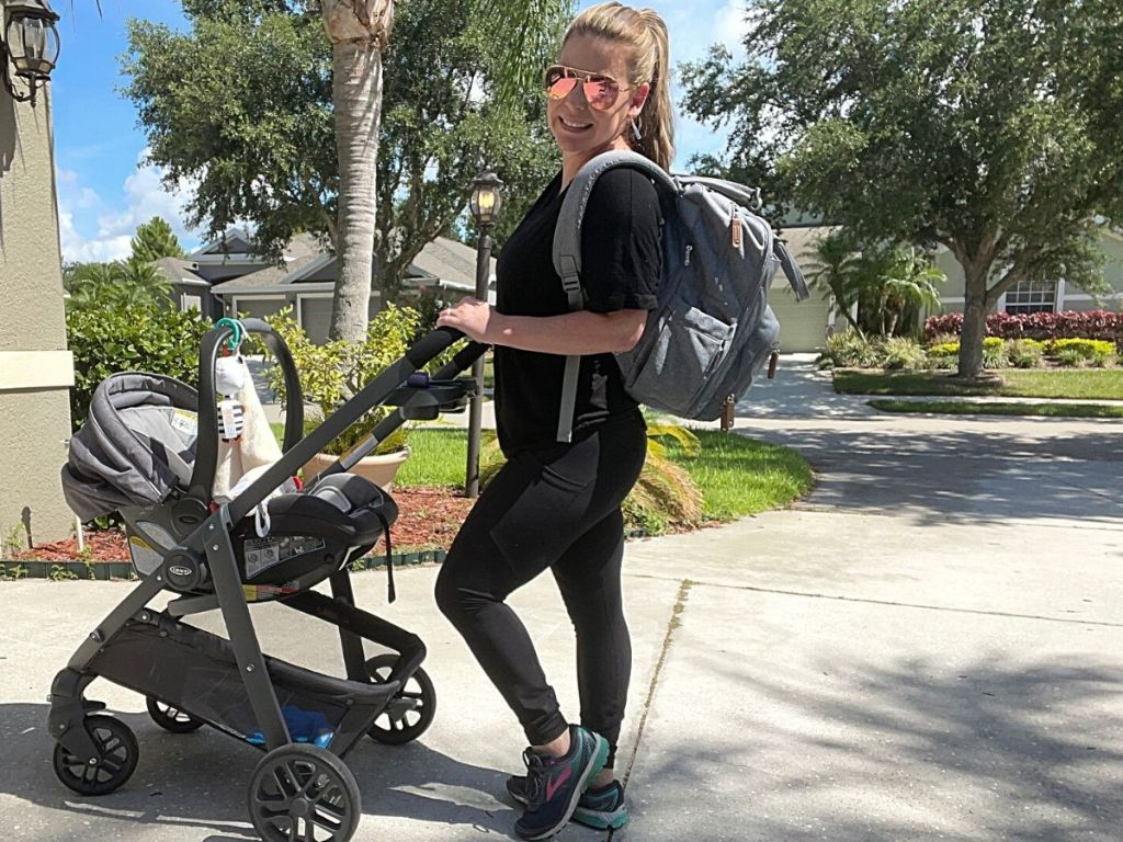 woman wearing sunglasses and gray diaper bag backpack pushing stroller