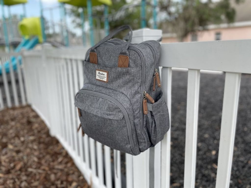 gray backpack diaper bag hanging on white fence