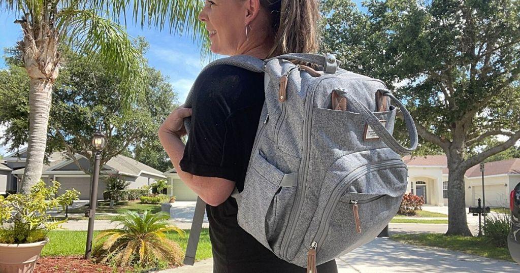woman carrying gray dipper bag backpack