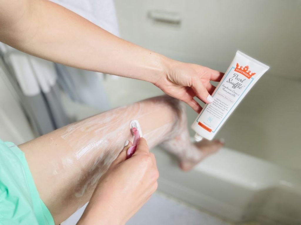 woman shaving her legs with one hand and holding Shaveworks shaving cream with the other